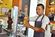 Cheerful Laxman pouring beer for a client